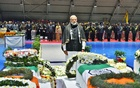 India's Prime Minister Narendra Modi pays tribute as he stands next to the coffins containing the remains of Central Reserve Police Force (CRPF) personnel who were killed after a suicide bomber rammed a car into a bus carrying them in south Kashmir on Thursday, at Palam airport in New Delhi, India, February 15, 2019. India's Press Information Bureau/Handout via REUTERS
