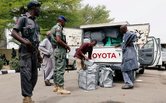 Police members oversee Ad-hoc staff loading boxes onto a truck during the distribution of election materials at the INEC office in Yola, Adamawa State, Nigeria Feb 15, 2019. REUTERS/Nyancho NwaNri