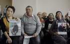 Clients of Atajurt Kazakh Human Rights, an activist group, with photographs of family members who have disappeared in China, in Almaty, the capital of Kazakhstan, Jan 12, 2019. The New York Times