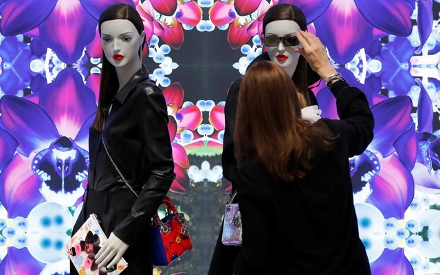 A shop assistant adjusts Dior sunglasses at Dior's new flagship store in London, Britain, May 31, 2016. Reuters