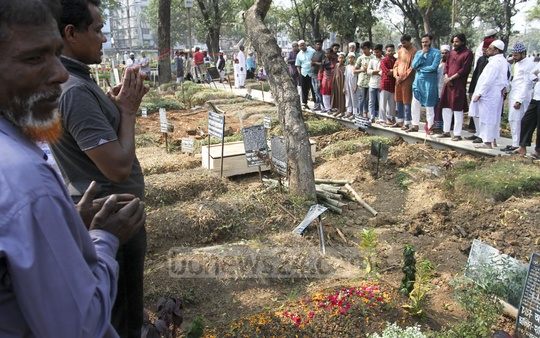 Loved ones visit the graves of Old Dhaka fire victims at Dhaka's Azimpur Graveyard on Friday. Photo: Asif Mahmud Ove