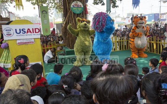 Children watch the Sisimpur, the Bangladeshi version of the globally-beloved children's puppet show, at the book fair on Saturday.