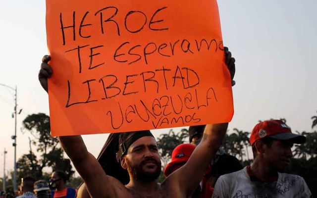 A demonstrator holds a placard that reads,