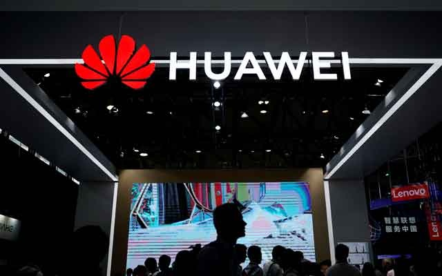 FILE PHOTO: People walk past a sign board of Huawei at CES (Consumer Electronics Show) Asia 2018 in Shanghai, China Jun 14, 2018. REUTERS