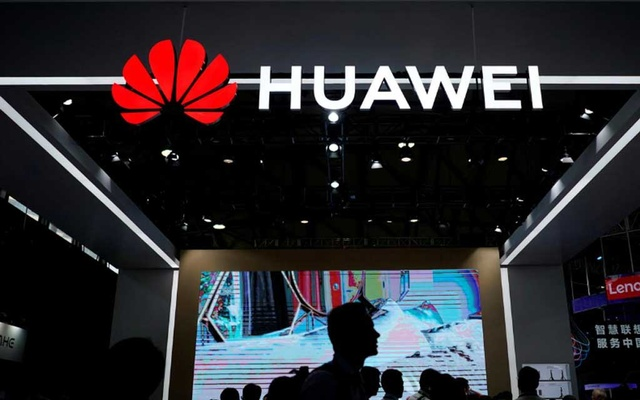 FILE PHOTO: People walk past a sign board of Huawei at CES (Consumer Electronics Show) Asia 2018 in Shanghai, China June 14, 2018. REUTERS