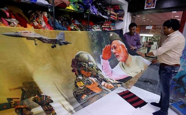 Traders display a sari, a traditional clothing worn by women, with printed images of India's Prime Minister and Indian Army inside their shop in Surat, India, March 8, 2019. Reuters
