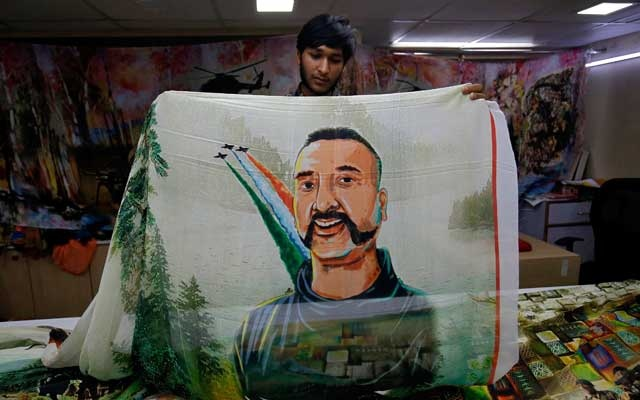 A salesman displays a sari, a traditional clothing worn by women, with a printed image of Indian Air Force pilot Abhinandan Varthaman, who was captured and later released by Pakistan, inside a sari manufacturing factory in Surat, India, March 8, 2019. Reuters