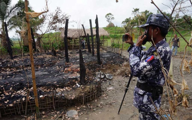 File Photo: A Myanmar border guard police officer takes pictures at the remains of a burned house in Tin May village, northern Rakhine state, Myanmar July 13, 2017. Picture taken July 13, 2017. Reuters