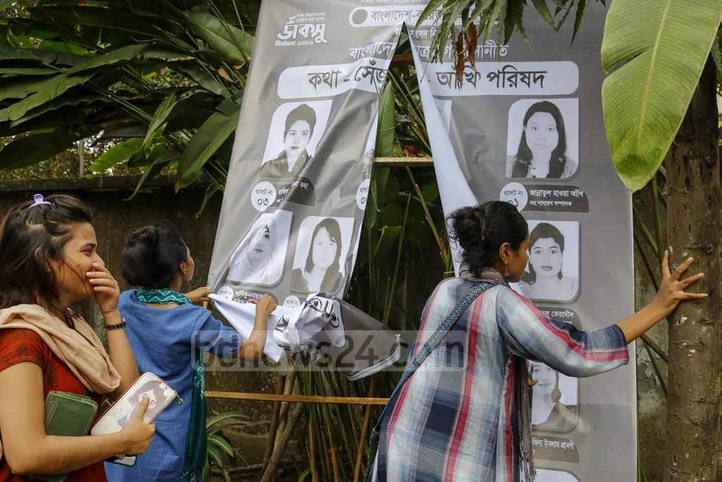 Agitated students tear down a panel's banner after the discovery of marked Hall Council ballot papers at Bangladesh-Kuwait Maitree Hall on Monday before DUCSU polls opened. Photo: Mostafigur Rahman