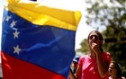A woman whistles as she and others block a street to show their anger because of the ongoing blackout in Caracas. REUTERS