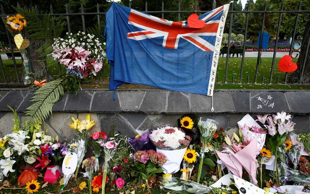Flowers and a New Zealand national flag are seen at a memorial as tributes to victims of the mosque attacks near Linwood mosque in Christchurch, New Zealand, Mar 16, 2019. REUTERS/Edgar Su