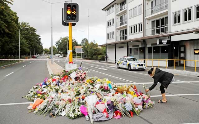 A woman places flowers at a memorial as a tribute to victims of the mosque attacks, near a police line outside Masjid Al Noor in Christchurch, New Zealand, Mar 16, 2019. REUTERS