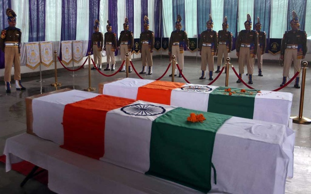 India's Central Reserve Police Force (CRPF) personnel stand behind the coffins of their two colleagues, who according to police were killed during a gun battle with militants in north Kashmir's Kupwara district on Friday, during a wreath-laying ceremony on the outskirts of Srinagar Mar 2, 2019. REUTERS/Danish Ismail