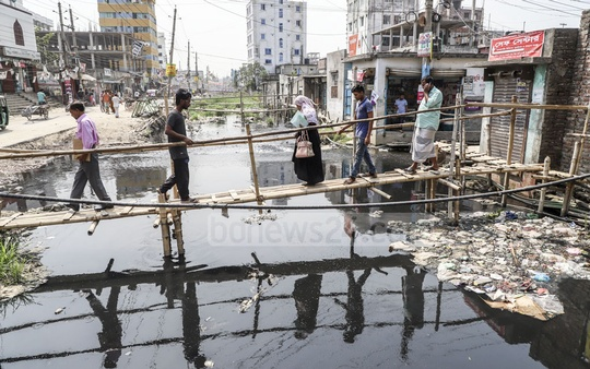 Makeshift bamboo bridges have been built over the canal on the Zia Swarani in Dhaka's Shonir Akhra for local residents. Photo: Abdullah Al Momin