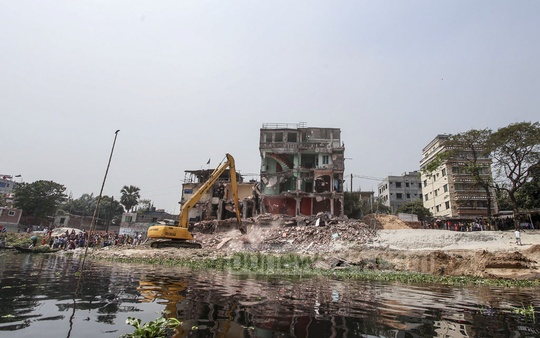 BIWTA bulldozing illegal buildings on the banks of the Turag river at Savar's Kaundia on the 22nd day of an eviction drive on Monday.