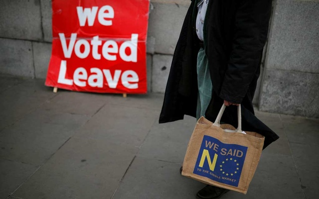 An anti-Brexit supporter stands in front of a pro-Brexit sign in London, Britain, March 27, 2019. Reuters