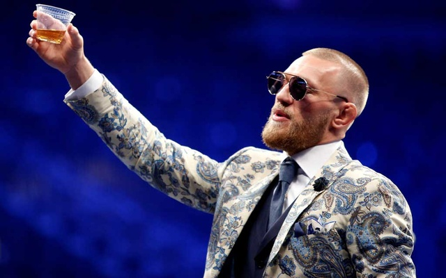 FILE PHOTO: UFC lightweight champion Conor McGregor of Ireland raises a cup of Irish whiskey during post-fight news conference at T-Mobile Arena in Las Vegas, Nevada, US Aug 27, 2017. REUTERS