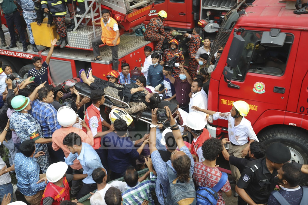 Rescuers carrying people injured in a fire at the FR Tower in Dhaka's Banani on Thursday. Photo: Asif Mahmud Ove