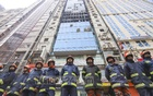 Fire service personnel stand in front of the 23-storey FR Tower in Banani on Friday, a day after the devastating fire swept through the high-rise. Photo: Asif Mahmud Ove