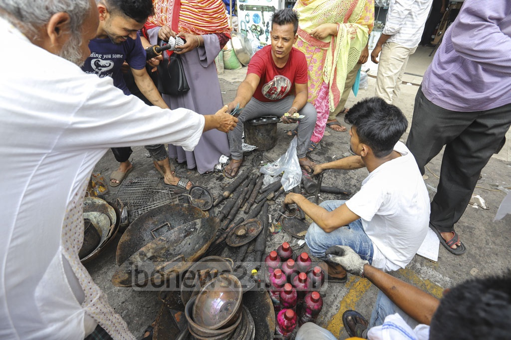 Customers on Sunday crowded to buy kitchenware burnt in a fire that gutted over 150 shops in a makeshift market adjacent to the DNNC Market in Gulshan-1 on Saturday. Photo: Asif Mahmud Ove