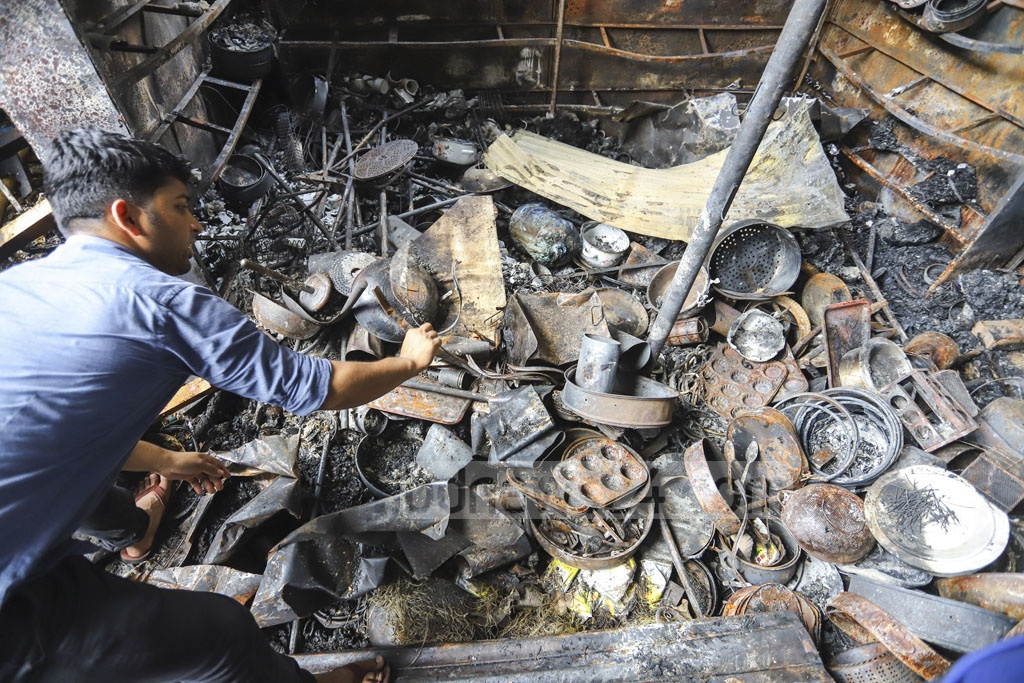 Shopkeepers on Sunday taking out goods burnt in a fire at a makeshift market adjacent to the DNNC Market in Gulshan-1 on Saturday. Photo: Asif Mahmud Ove