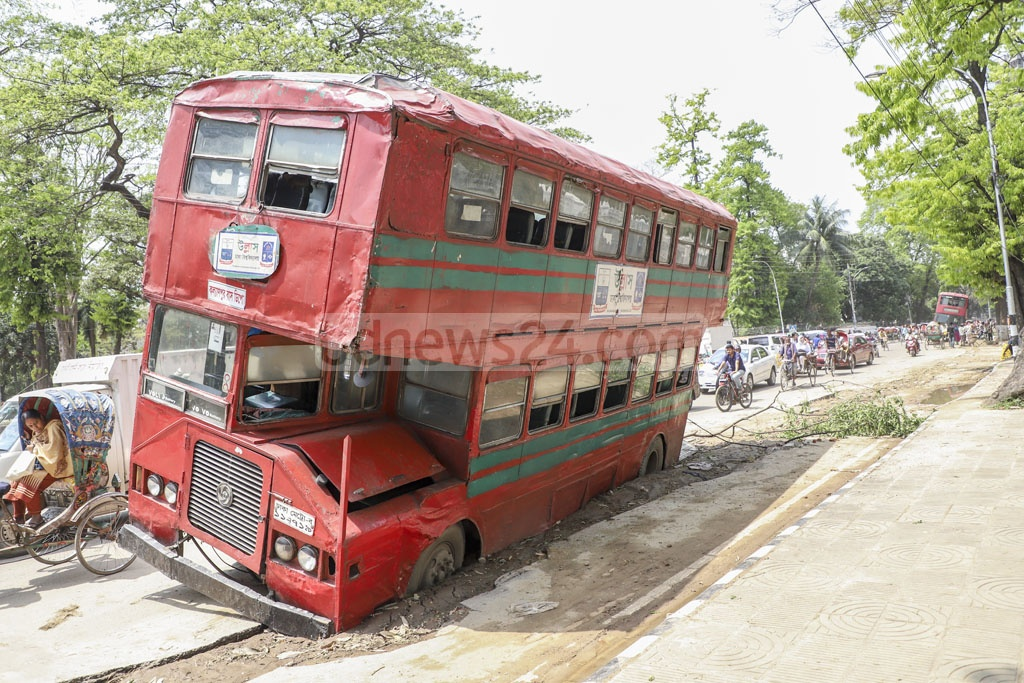 Two Dhaka University double decker buses tilted as their left wheels got stuck in a part of the street dug for laying electricity lines near the Central Shaheed Minar on Monday. Photo: Abdullah Al Momin