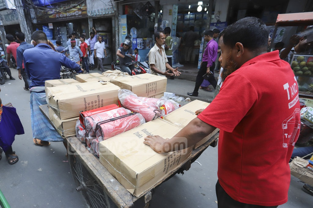 People transporting fire extinguishers bought from a wholesale market in Dhaka's Nawabpur on Tuesday. Photo: Asif Mahmud Ove