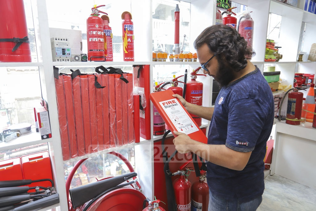A customer checking a fire extinguisher at a Nawabpur wholesale market shop in Dhaka on Tuesday. Photo: Asif Mahmud Ove