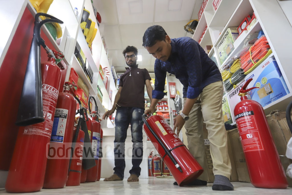 A shopkeeper arranging fire extinguishers at a wholesale market in Dhaka's Nawabpur on Tuesday. Photo: Asif Mahmud Ove