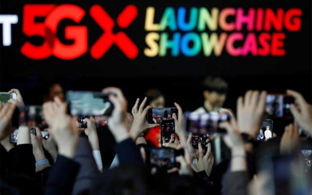 People take photographs during a launching ceremony for SK Telecom's 5G service, in Seoul, South Korea, Apr 3, 2019. REUTERS