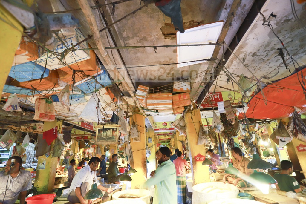 Traders and customers put their lives in danger to trade fish at a market in Dhaka's Kaptan Bazar as the run-down building is at risk of collapse any time. Many had been injured at different times from debris falling from the roof. Photo: Abdullah Al Momin