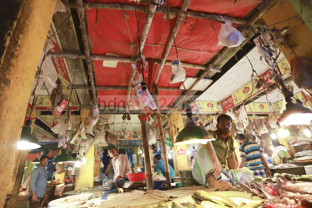 Traders set up a dropped ceiling to save themselves from falling debris of a run-down fish market in Dhaka's Kaptan Bazar. Photo: Abdullah Al Momin