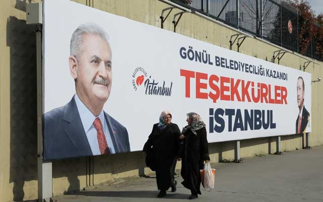 Turkish election: People walk past by AK Party billboards with pictures of Turkish President Tayyip Erdogan and mayoral candidate Binali Yildirim in Istanbul, Turkey, Apr 1, 2019. The billboards read: