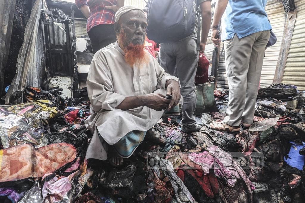 A shopkeeper sits on a stack of burnt clothes after a fire gutted shops at the Kamarpotti market, close to the Khilgaon Rail Gate in Dhaka, on Thursday.