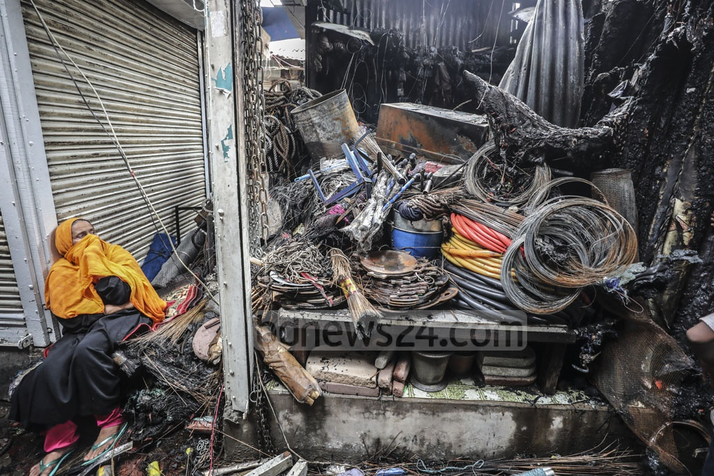 A woman sits in front of a burnt shop owned by her son at the Kamarpotti market, close to the Khilgaon Rail Gate in Dhaka, on Thursday