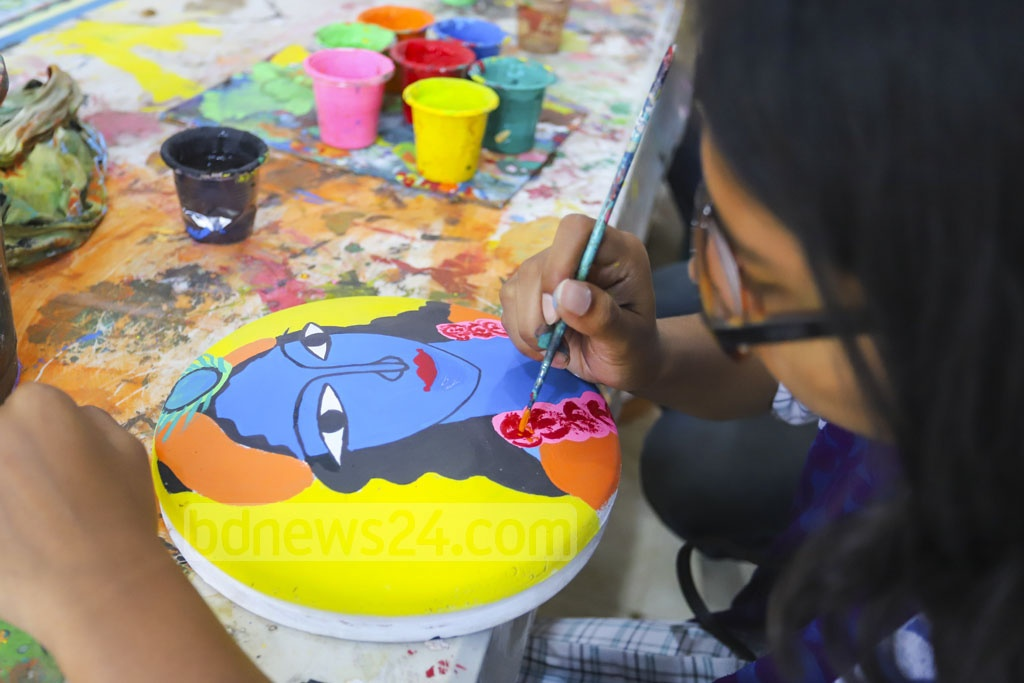 A student of Dhaka University's Faculty of Fine Arts painting a pot for Bangla New Year celebrations on Friday. Photo: Asif Mahmud Ove