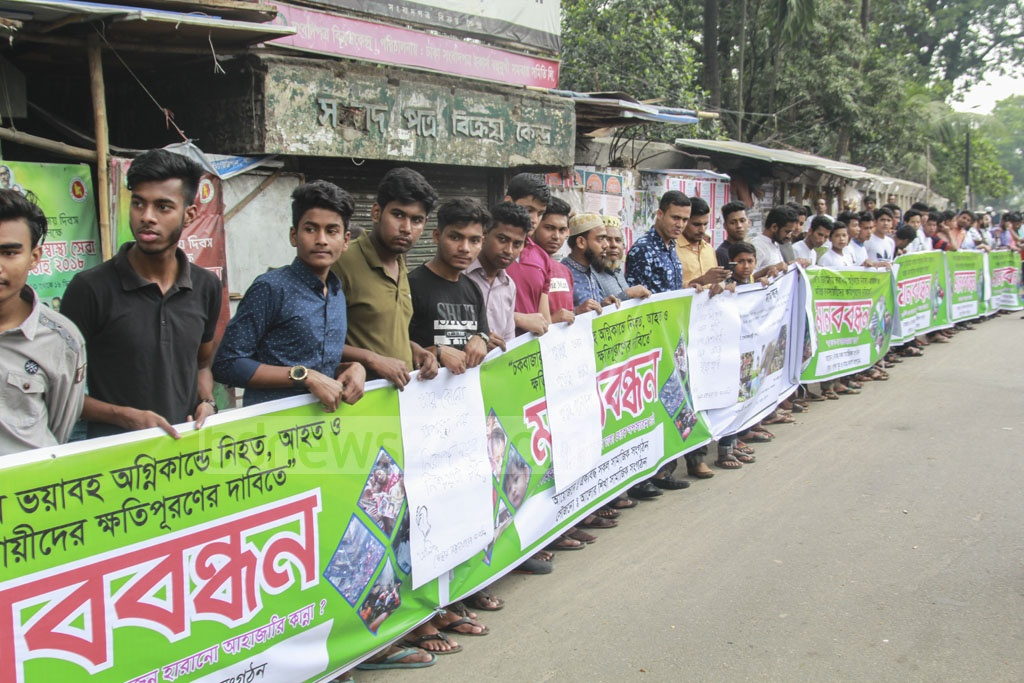 Social welfare organisations take part in a human chain programme to demand compensation for those affected by the Chawkbazar fire in front of the National Press Club on Friday.