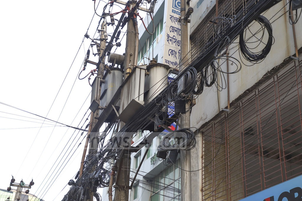 NOTHING WIRELESS ABOUT IT: Cobwebs of wires for internet, telephone, cable TV and other connections hang dangerously along high-voltage electricity wires in Dhaka despite court orders to remove these, which often cause fire. This photo was taken at Mohakhali, near an area named Wireless, on Sunday. Photo: Abdullah Al Momin