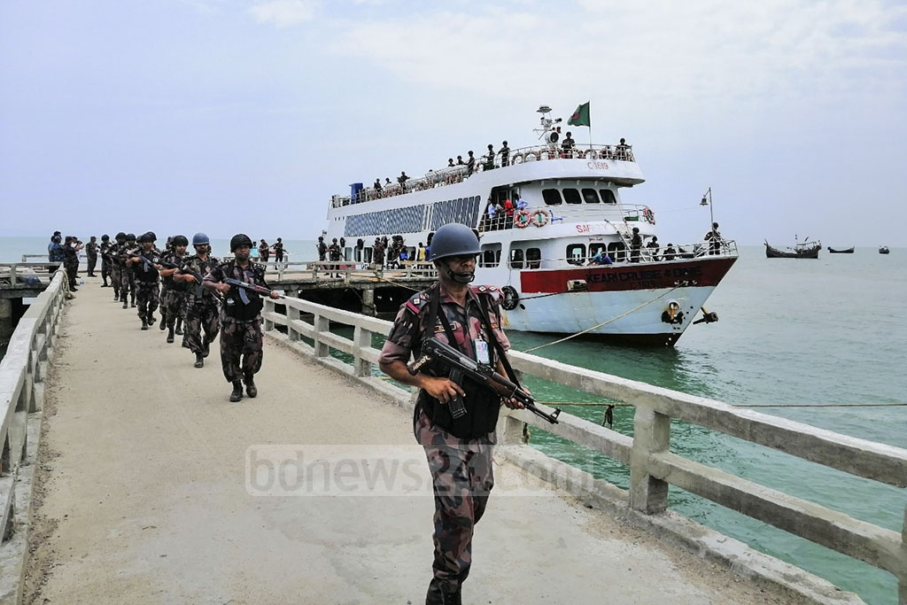 Border Guard Bangladesh personnel walking in a file after getting off a ship on Saint Martin's Island on Sunday. The authorities have deployed BGB troopers in the island after 22 years.