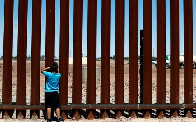 FILE PHOTO: A child looks through the border wall during the visit of US President Donald Trump to Calexico, California, as seen in Mexicali, Mexico Apr 5, 2019. REUTERS/Carlos Jasso/File Photo