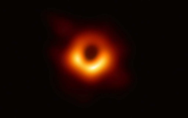 The first ever photo a black hole, taken using a global network of telescopes, conducted by the Event Horizon Telescope (EHT) project, to gain insight into celestial objects with gravitational fields so strong no mater or light can escape, is shown in this handout photo released April 10, 2019. Event Horizon Telescope (EHT)/National Science Foundation/Handout via REUTERS