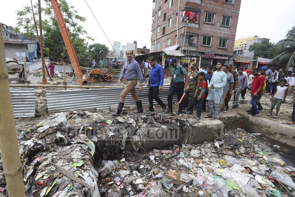 Dhaka North City Corporation workers scavenging a canal called Sangbadik Khal at Mirpur on Thursday as garbage there has been stopping water from receding on Purobi-Kalshi street. Photo: Asif Mahmud Ove