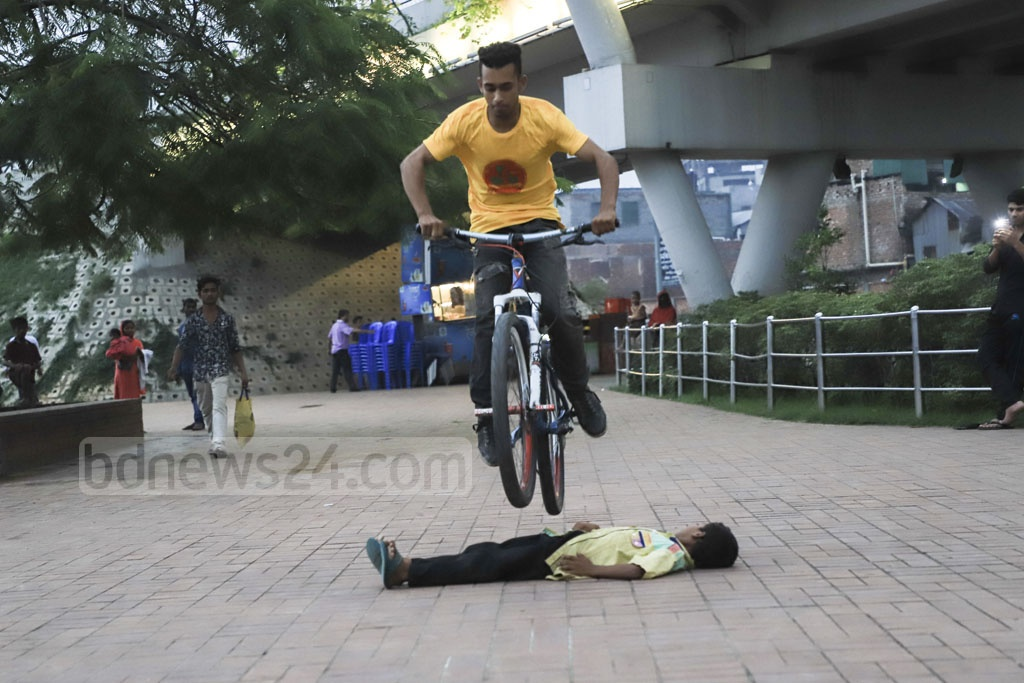 A teenaged boy is jumping over a lying child in a bicycle stunt in Hatirjheel area in Dhaka on Thursday. Photo: Abdullah Al Momin