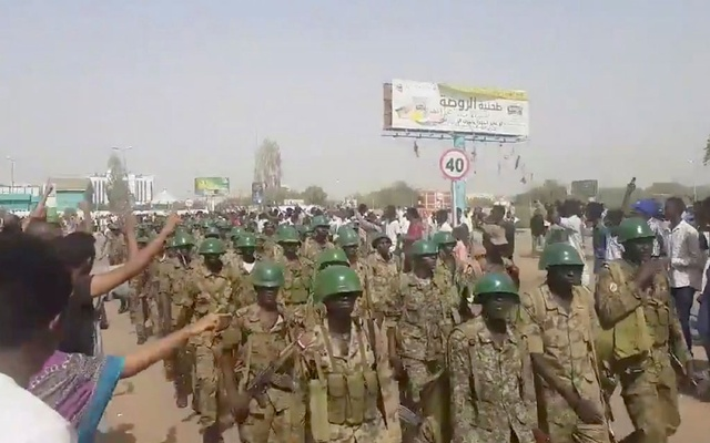 Demonstrators salute soldiers during a protest in Khartoum, Sudan April 10, 2019 in this still image taken from a video obtained from social media. TWITTER/@THAWRAGYSD/via REUTERS