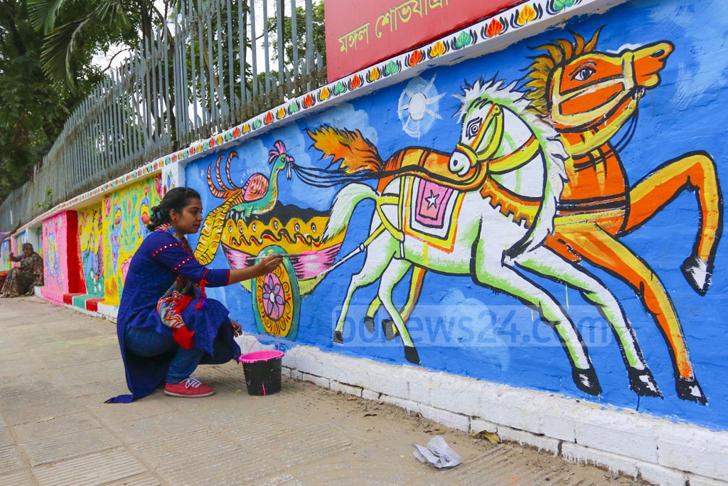 A student of Dhaka University's Faculty of Fine Arts paints an Alpona on the wall of the institution on the eve of Pahela Baishakh on Saturday. Photo: Abdullah Al Momin