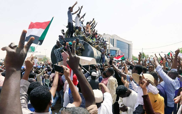 Sudanese military officers and demonstrators ride atop a military tanker as they protest against the army's announcement that President Omar al-Bashir would be replaced by a military-led transitional council, near Defence Ministry in Khartoum. REUTERS