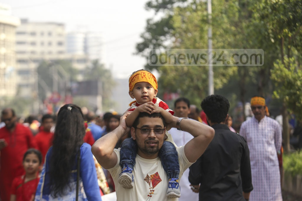 Bengalis revel in the Bangla New Year's festivities. Children join the Mangal Shobhajatra procession on their fathers' laps.