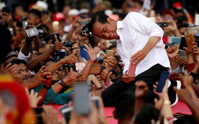FILE PHOTO: Indonesia's presidential candidate for the upcoming general election Joko Widodo takes pictures with his supporters during his first campaign rally at a stadium in Serang, Banten province, Indonesia, March 24, 2019. REUTERS/Willy Kurniawan/File Photo