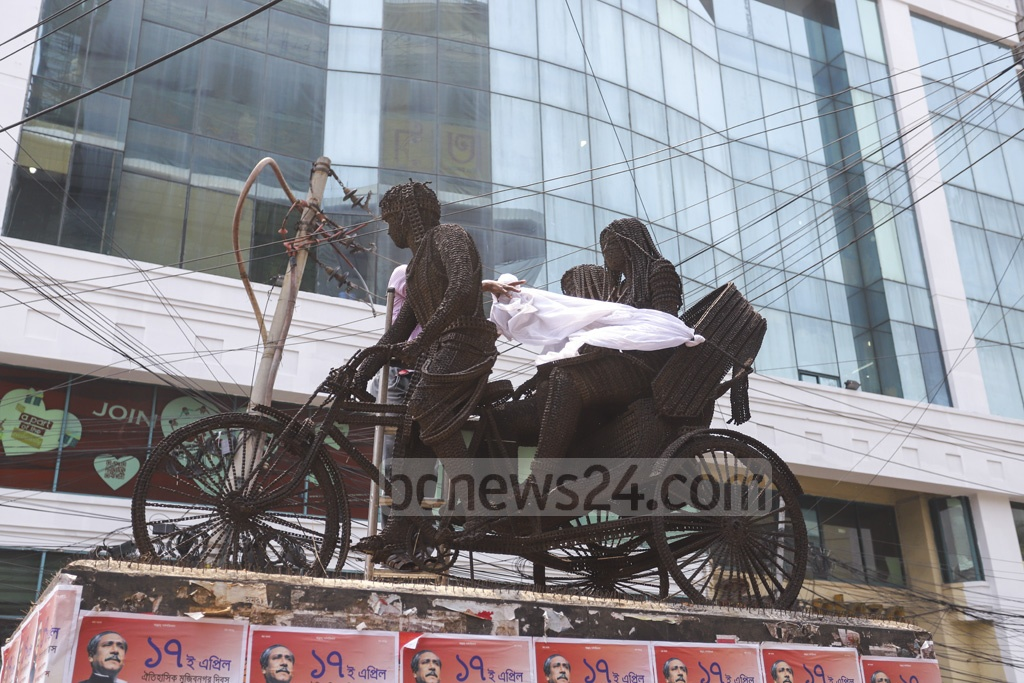 Dhaka City Corporation workers remove a piece of cloth covering the 'Ispater Kanna' sculpture at Dhanmondi Road No. 27 in Dhaka on Wednesday. Photo: Asif Mahmud Ove