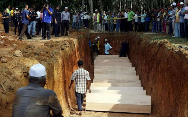 File Photo: A crowd gathers around a mass grave with the remains of unidentified Rohingya people found at a traffickers camp in Wang Kelian in Malaysia. Reuters